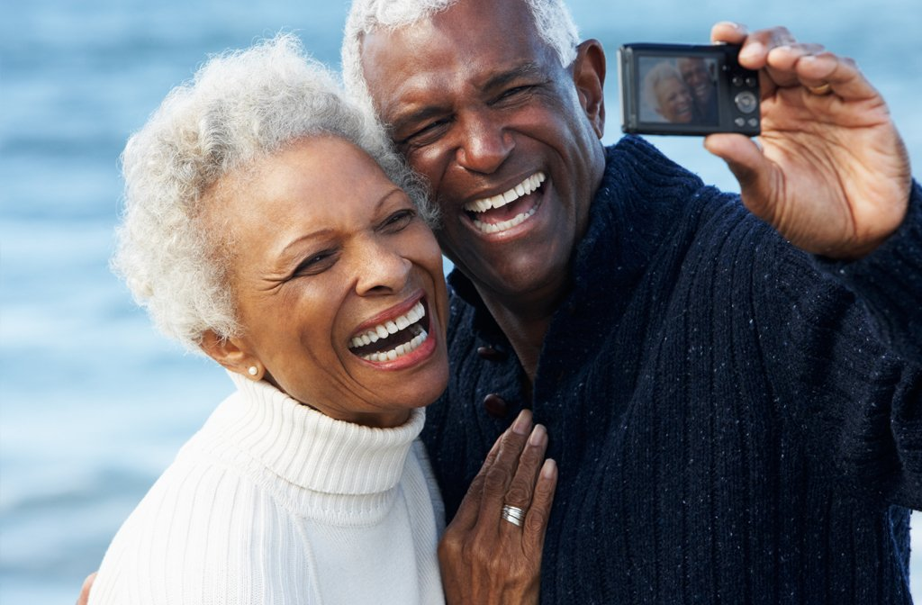 This is a picture of a couple happily living at San Diego Retirement Community Chateau La Jolla taking a selfie on the beach.