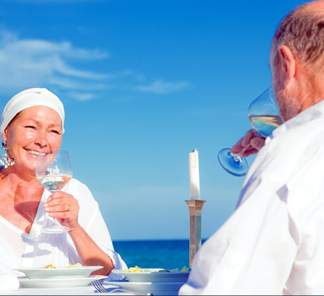 A picture of an older couple dining on the beach.