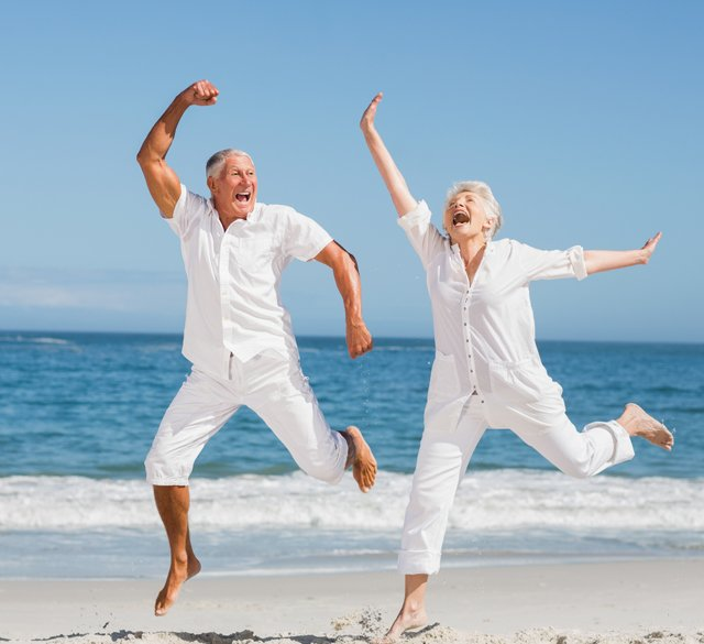 A picture of a happy older couple dancing on the beach.