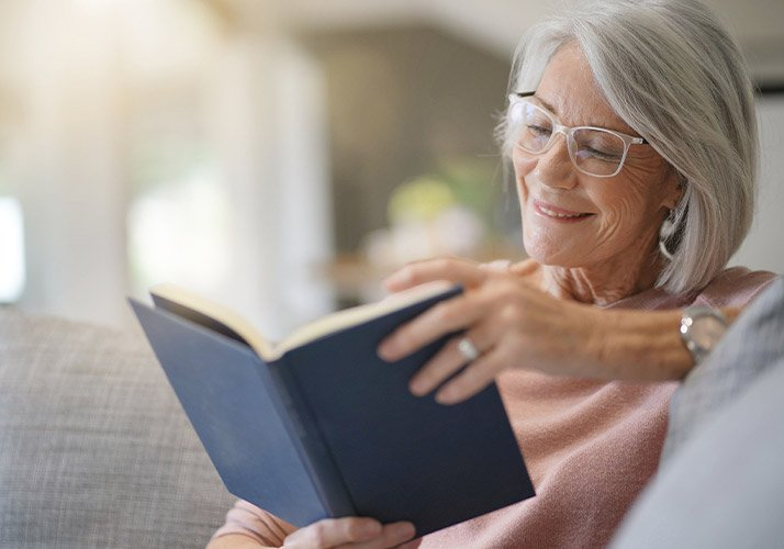 An Older Woman Reading A Book